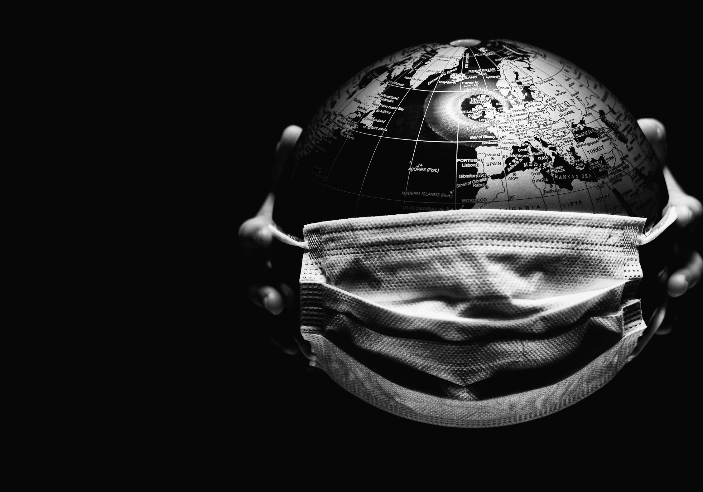 Hands of little child holding globe sphere, planet map covered with medical protective mask isolated on black background. Concept of COVID-19 pandemic infection